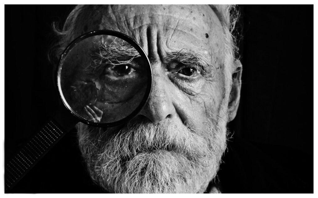 Gesicht eines alten Mannes, der ein Vergößerungsglas nutzt